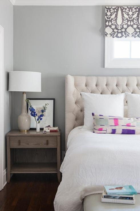 chic bedroom features a cream linen tufted wingback headboard on bed dressed in white linen bedding as well as pink and purple lumbar pillow placed under a