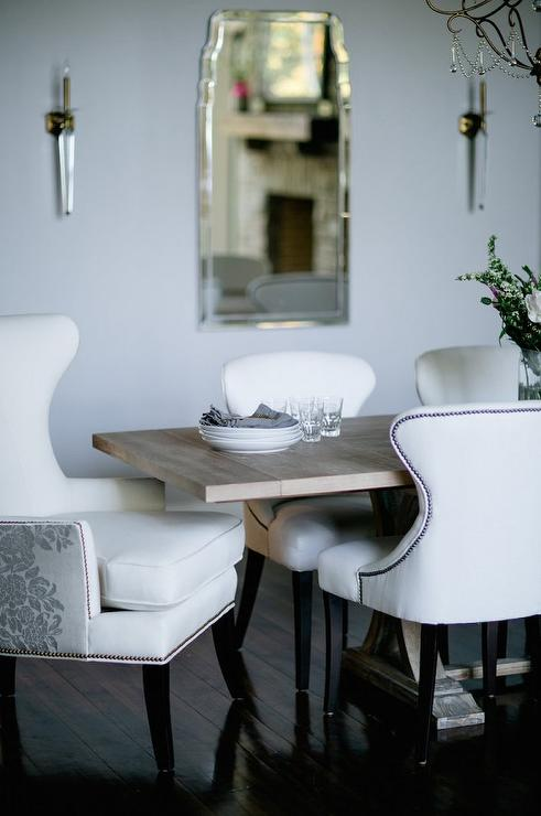 trestle dining table with white and gray embroidered wingback dining chairs