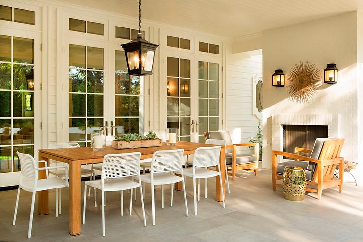 Covered Patio With Dining Space In Front Of White Brick Fireplace