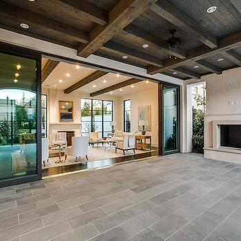 Covered Patio With Dark Stained Coffered Ceiling And Fireplace