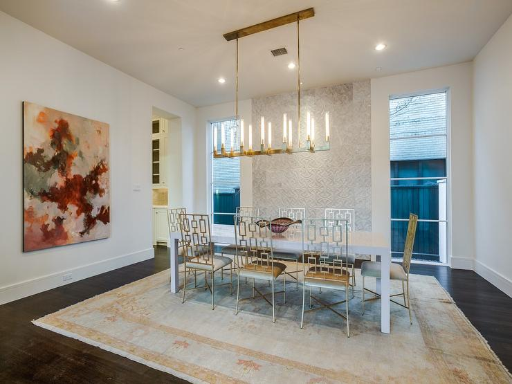 Contemporary Dining Room Features A Brass Linear Chandelier Suspended Over Glossy White Parsons Table Lined With Silver Leaf Chairs