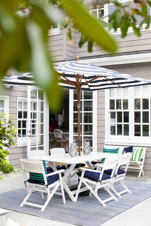 Enjoy Your Time Outdoors In This Beautiful Patio Featuring A Blue Rug  Positioned Beneath A White X Based Outdoor Dining Table Surrounded By White  Folding ...