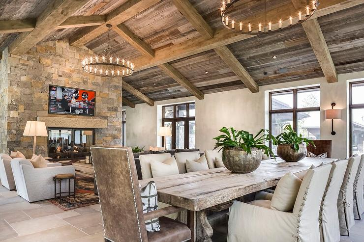 An iron candelabra hangs from a gorgeous rustic plank vaulted ceiling in  front of an inset TV niche positioned over a double sided stone fireplace  fitted ... - Living Room Vaulted Ceiling Design Ideas