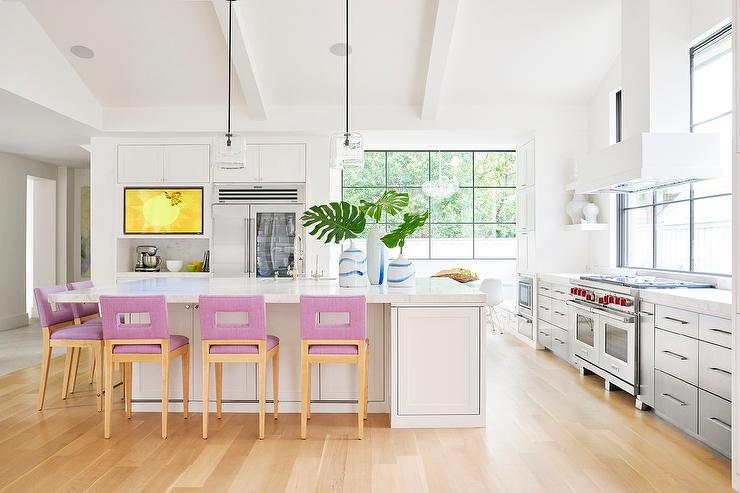 huge kitchen island with mauve bar stools and glass lanterns