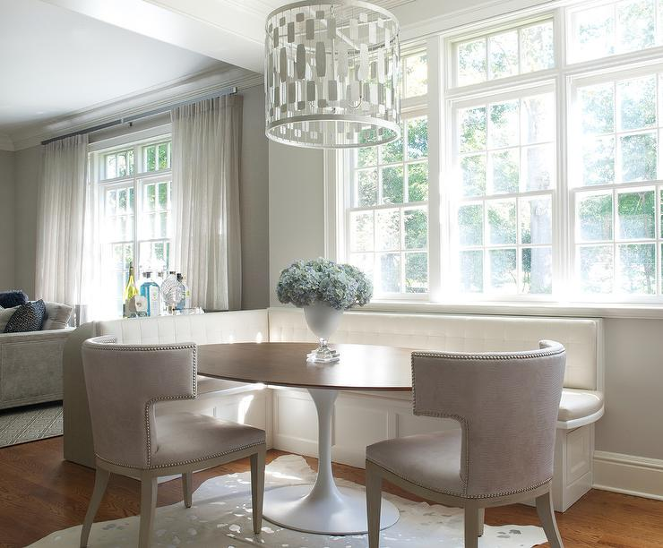 built in banquette sits against walls painted in benjamin moore pale oak under a window and partially frames an oval mid century pedestal dining table - Dining Room Table With Bench Against Wall
