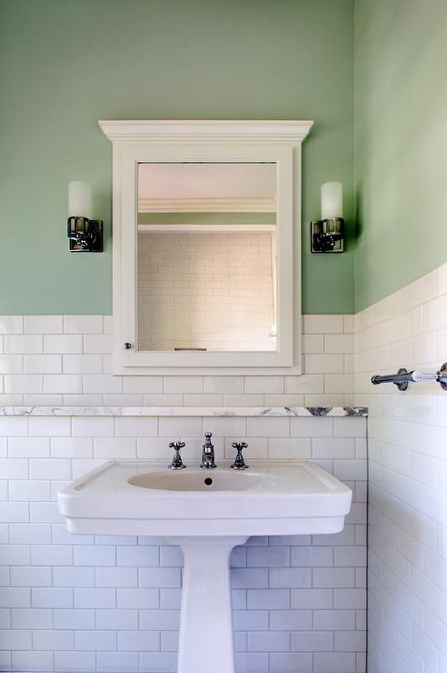 Charming white and green bathroom features wall clad in white subway tiles  on the lower walls and green upper walls lit by two sconces mounted on  either ...