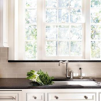Ivory Kitchen Cabinets With Black Granite Counters And Gray Subway Tiles