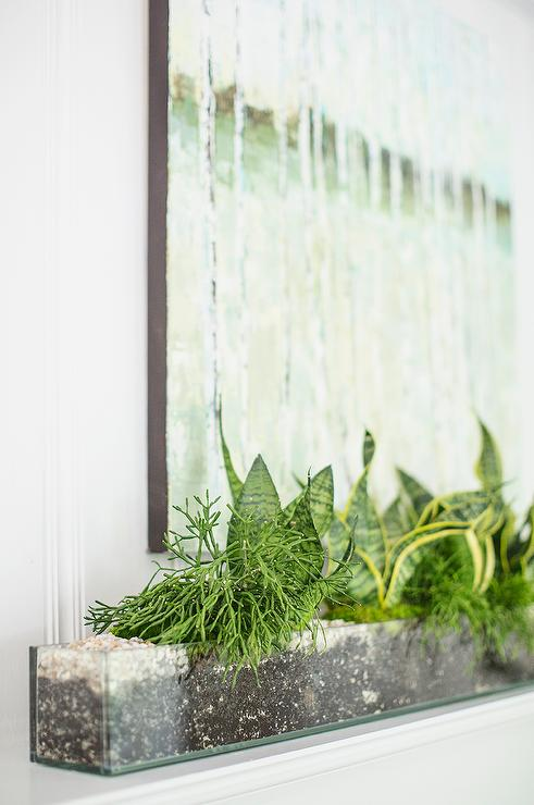 White Fireplace Mantle With Clear Trough Vase Filled With Succulents