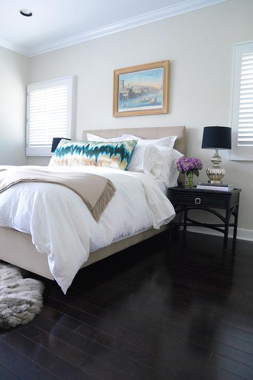 Between Square Windows Covered In Shades An Oil Painting Hangs Over A Beige Upholstered Bed Dressed In White Hotel Bedding Topped With A Gold And Teal Body