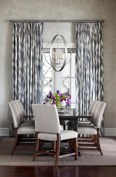 Blue And Gray Dining Room Features A Glossy Black Table Surrounded By Linen Chairs Positioned On Taupe Bound Sisal Rug Illuminated