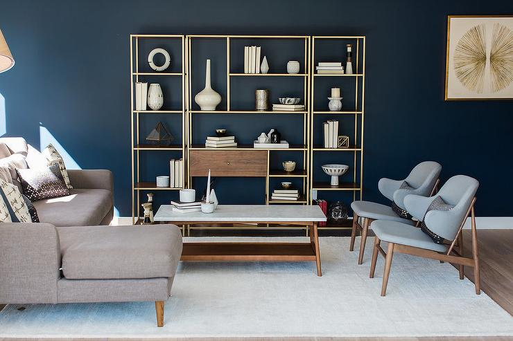 blue living room with wood and brass shelving unit - transitional