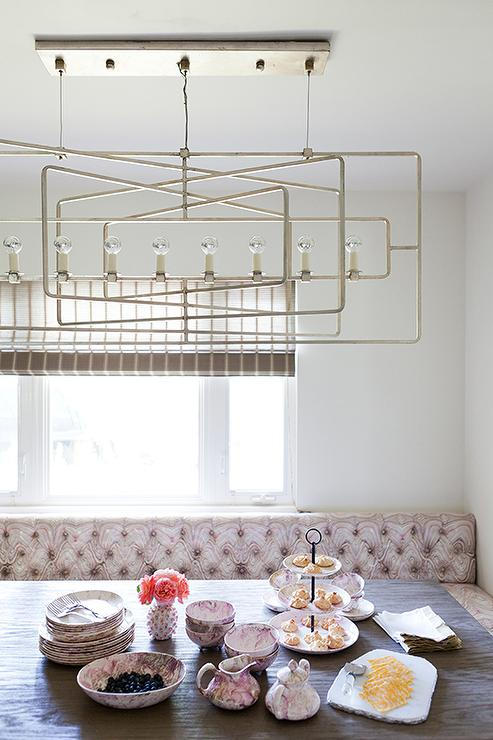 Long Pink Tufted Banquet Is Positioned Against A White Wall Framing Window Dressed In Sheer Beige Shade And Behind Wood Top Dining Table Illuminated