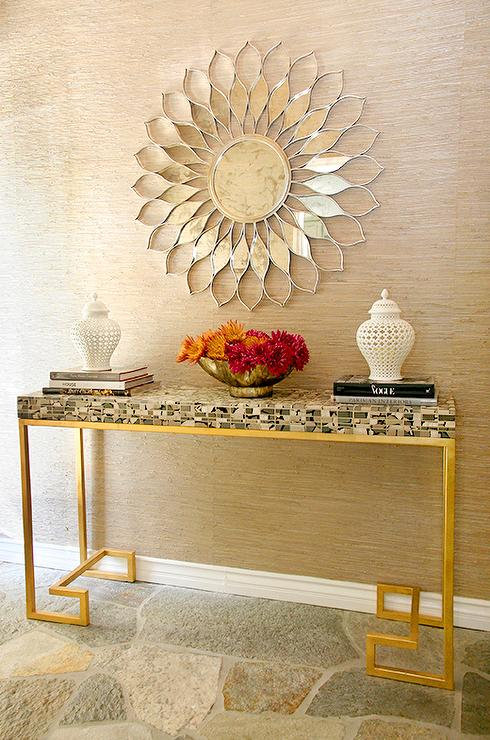 Positioned Against Tan Raffia Wallpaper, A Silver Sunburst Mirror Is  Mounted Over A Styled Green Mosaic Console Table With A Brass Greek Key  Base Topped ...
