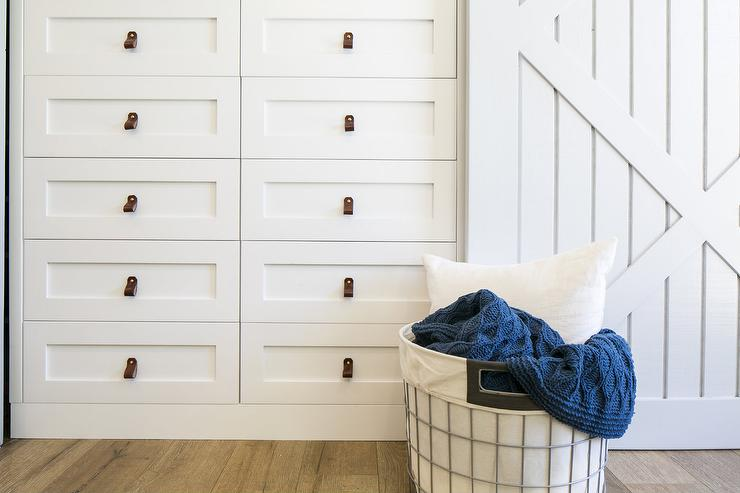 A 10 Drawer Built In White Dresser Adorns Leather Pulls And Is Positioned  Beside A Light Gray Closet Barn Door And Behind A Metal And Canvas Hamper.
