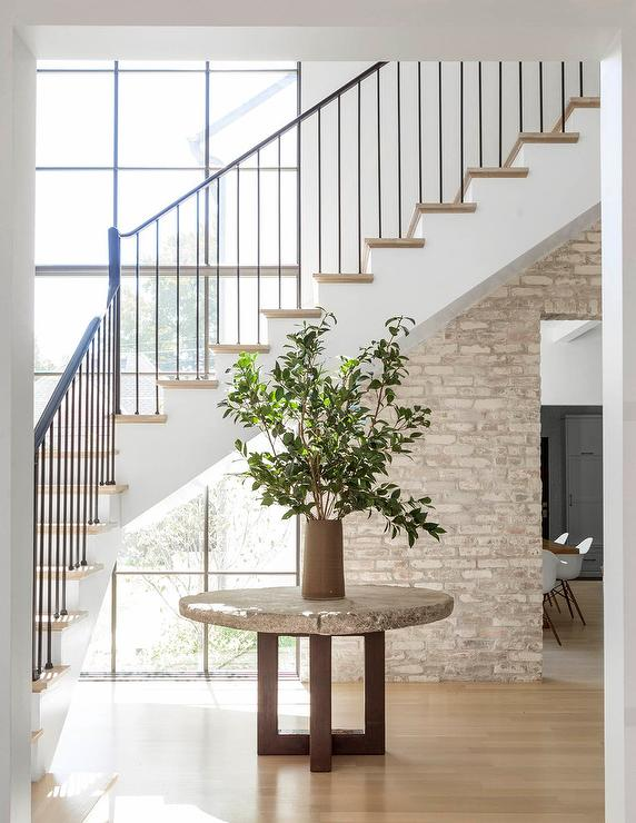 minimalist foyer boasts a round concrete table topped with a potted plant and positioned in front of white staircase finished with an iron handrail and