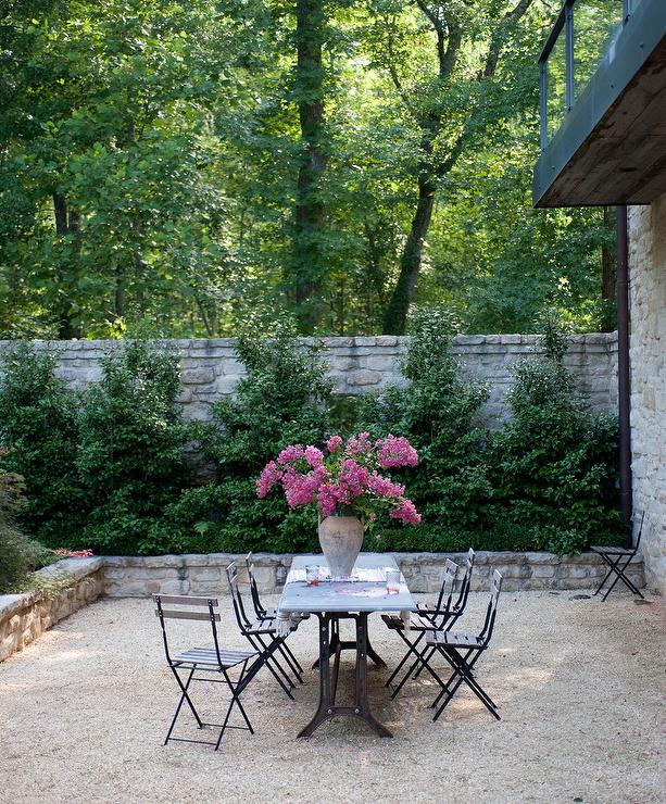 high stone wall garden with rectangular french marble bistro table