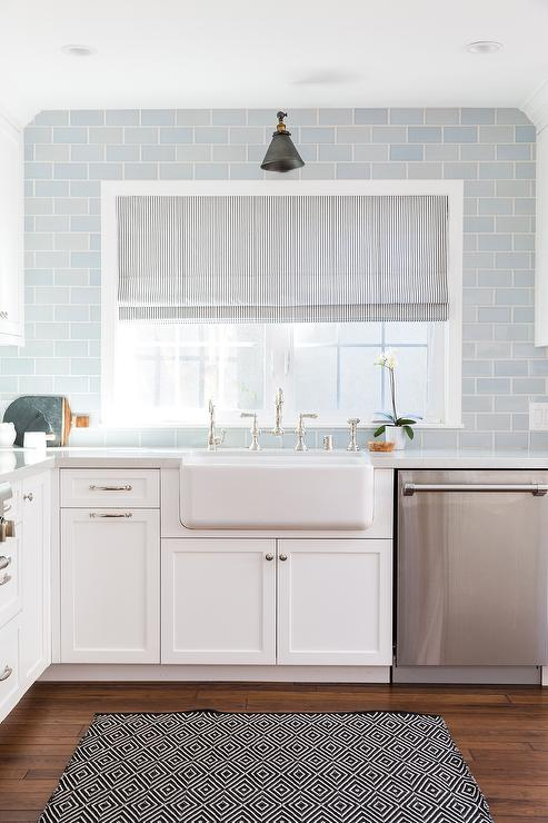 White and blue kitchen boasts white shaker cabinets paired with blue
