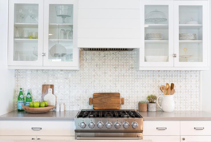 White And Gray Kitchen Feature White Cabinets Paired With Gray Quartz Countertops And A Gray Mosaic Tile Backsplash
