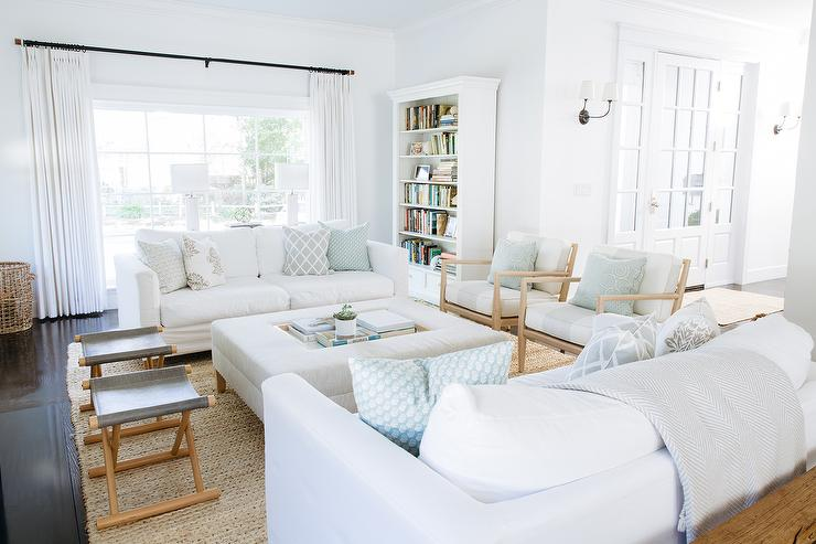 ... Slipcovered Sofas Lined With Gray And Blue Pillows Facing Each Other  Across From A White Ottoman Fitted With A Recessed Tray Doubling As A Coffee  Table.