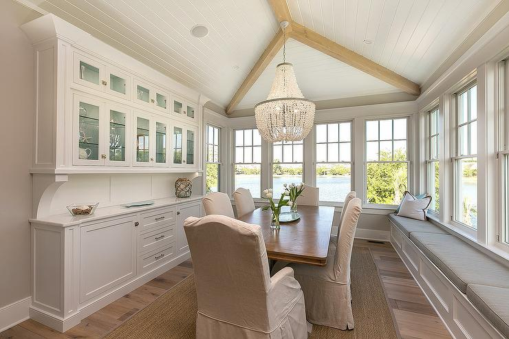 Elegant Cottage Dining Room Features A White Beaded Chandelier Hung From Vaulted Plank Ceiling Over Rectangular Wood Table Surrounded By Natural