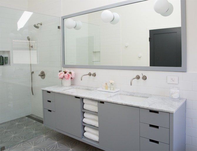 amazing gray bathroom features a gray floating dual washstand topped with gray and white marble fitted with his and hers sinks tucked under satin nickel