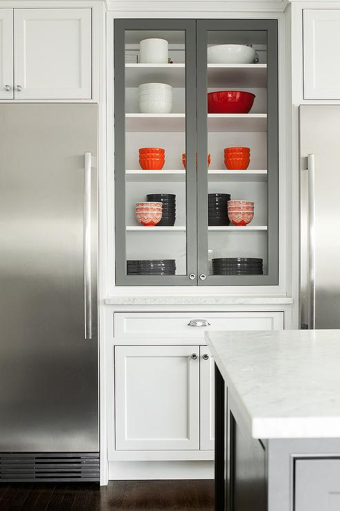 white and gray kitchen features a white builtin china cabinet finished with gray glass front doors flanked by stainless steel matching tucked