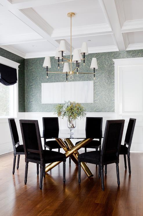 dramatic square back black velvet french dining chairs surround a round glass top gold based dining table positioned under a jonathan adler ventana two tier