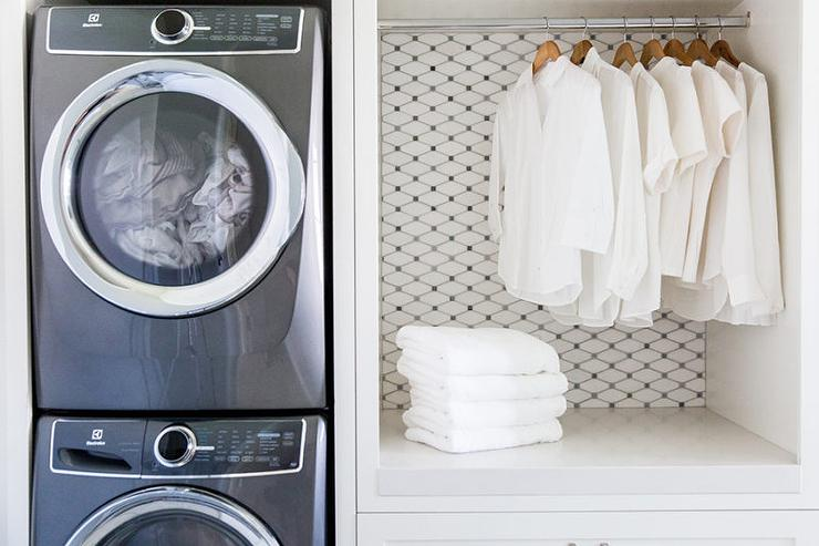 stacked enclosed washer and dryer next to folding station