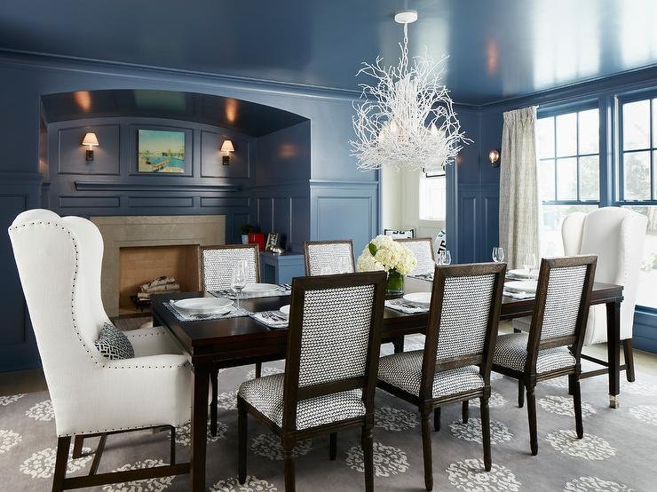 blue dining room with black dining table and white leather dining