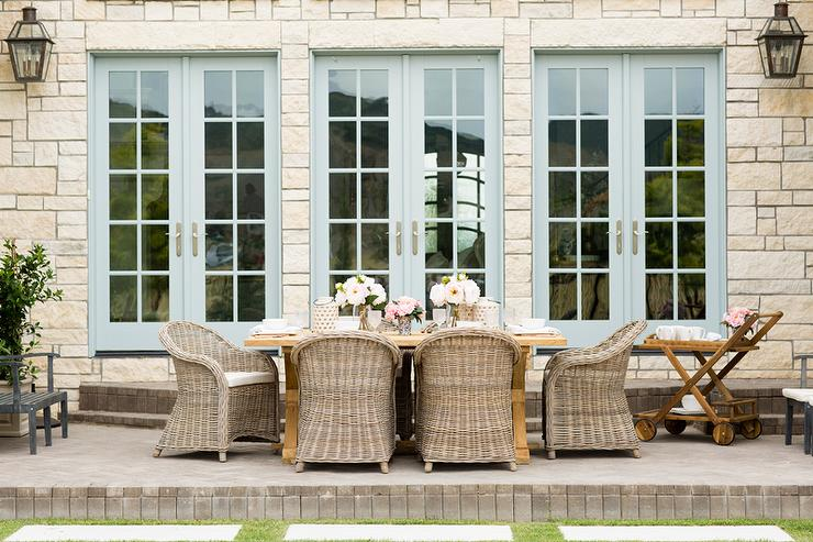 Powder Blue French Doors Open To A Stunning Patio Boasting Wicker Dining  Chairs Seated Around A Trestle Dining Table Positioned In Front Of Grass  Pavers.
