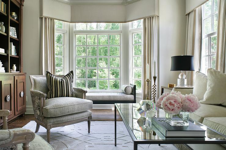 beautifully furnished light gray and ivory living room boasts a black chaise lounge bench placed in front of bay windows dressed in light gray linen cornice