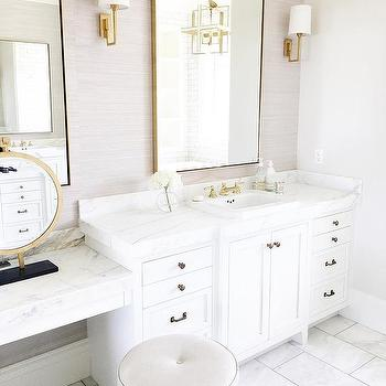 white and gray bathroom with brass mirror and sconces