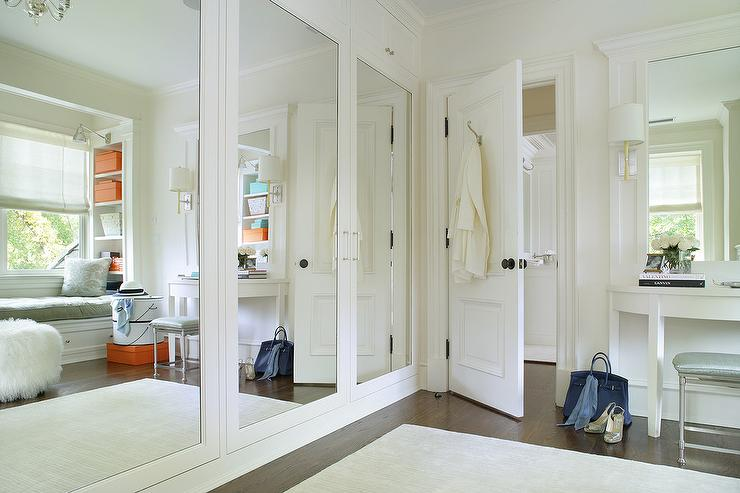 White Walk In Closet With Orange Accents Features A Wall Lined Mirrored Wardrobe Doors Reflecting Area Rug And Half Moon Vanity Table