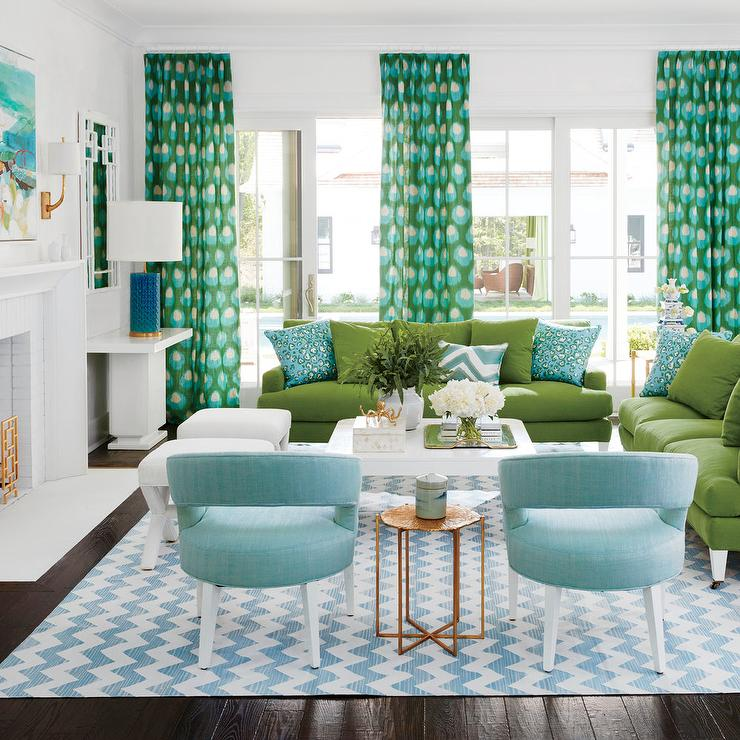 Blue And Green Living Room Features Two Sofas Lined With Turquoise Pillows Facing A White Lacquered Coffee Table Placed Atop