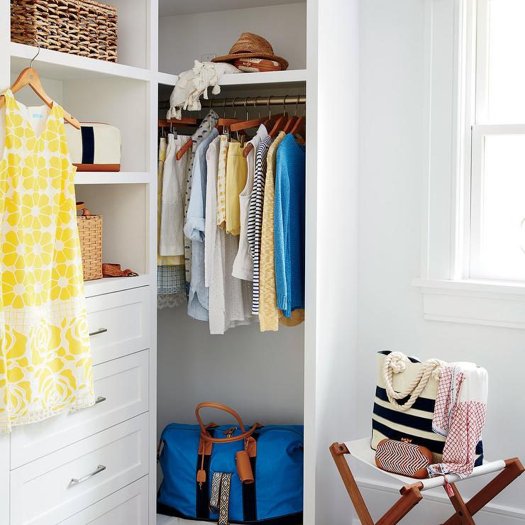 Chic Walk In Closet Features White Shelves Over A White Built In Dresser  Alongside A White Folding Camp Stool.