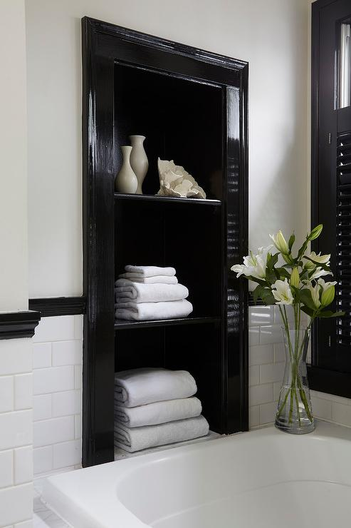 Attrayant Above A Drop In Tub, A Glossy Black Niche Fitted With Shelves Holds Stacked  Towels And Is Framed By White Subway Backsplash Tiles Lined With A Black  Chair ...