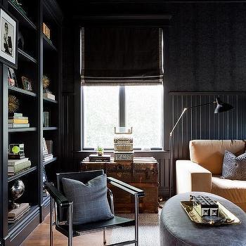black beadboard den walls with black built in bookshelves