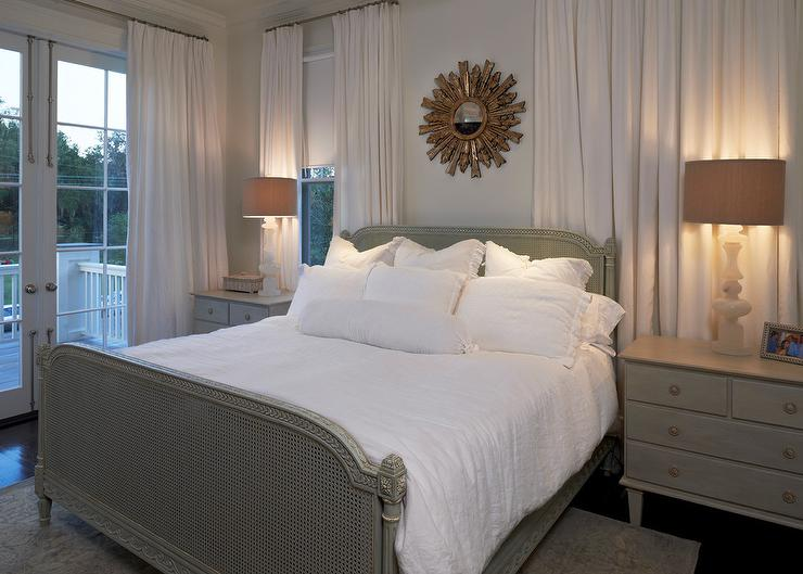 Gold Sunburst Mirror Over Gray Cane Bed With Footboard