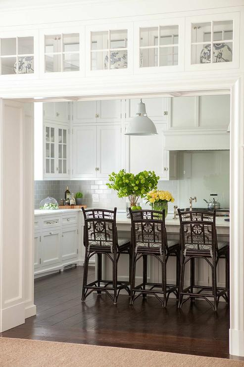 A kitchen doorway is fitted with glass display cabinets leading to a beautiful kitchen filled with white shaker cabinets paired with white marble ... & Gray Wash Cane Bar Stool Design Ideas islam-shia.org