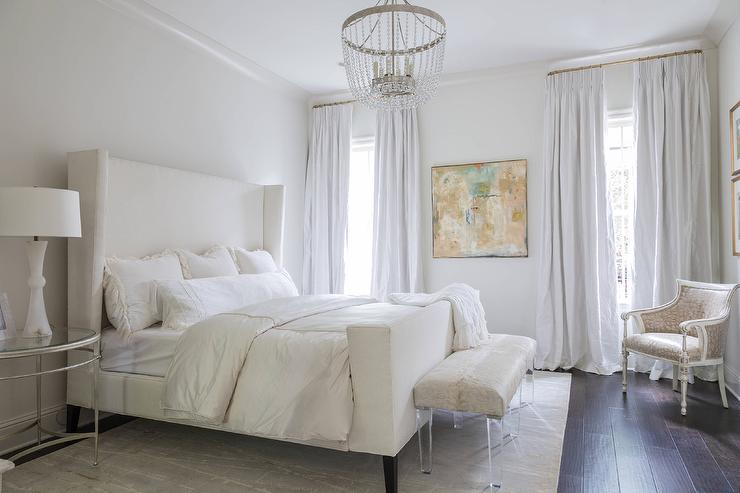 white wingback bed with marble lamps