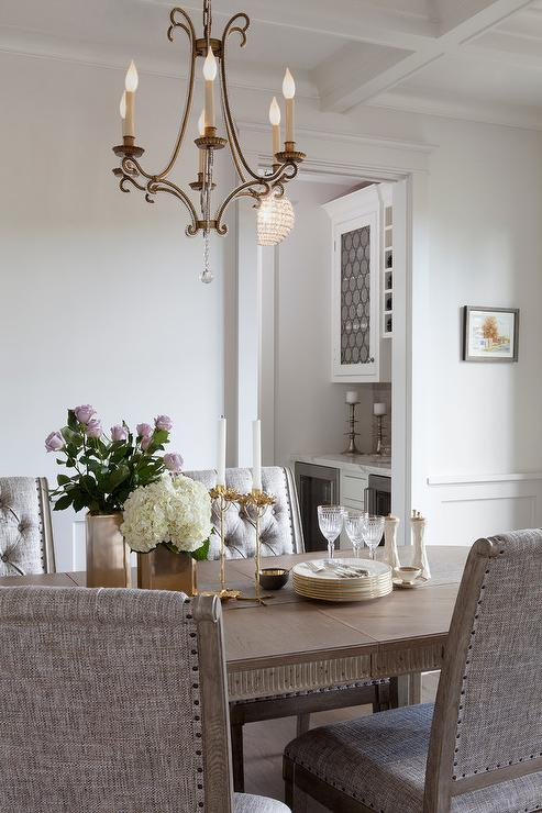Chandelier Is Fixed Above A Honey Stained Oval Dining Table Topped With Brass Vases And Candle Holders Surrounded By Gray Upholstered Chairs