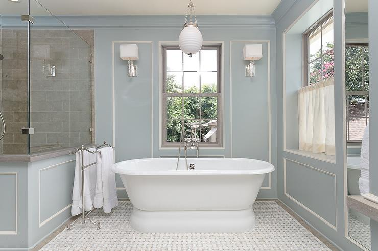 Freestanding tub under window dressed in blue cafe for Roberts designs bathroom accessories