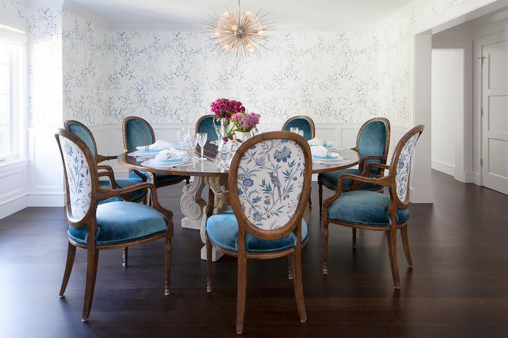 An Elegant Blue And White Dining Room Features A Arteriors Zanadoo Chandelier Hung Above Round French Table Surrounded By Velvet Chairs
