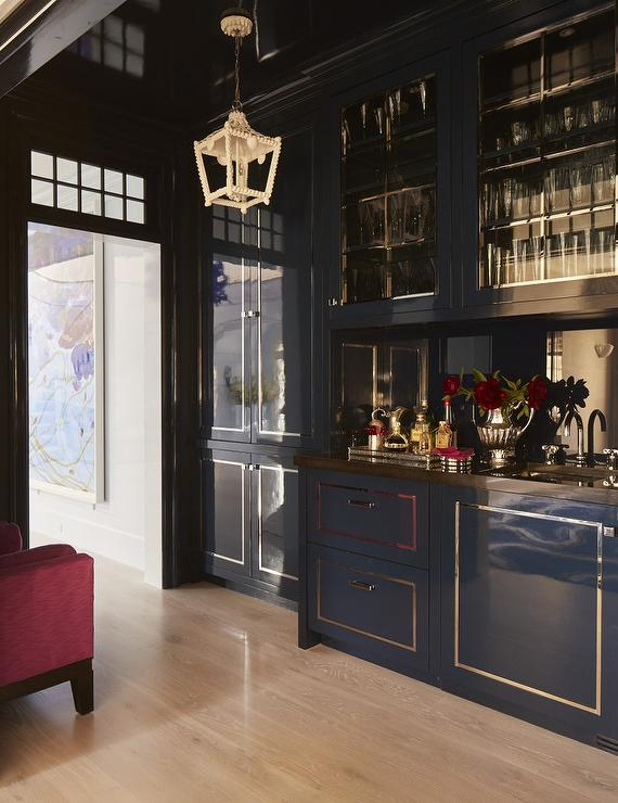 chic wet bar boasts blue lacquered cabinets accented with a gold trim and a brown countertop fitted with a sink and polished nickel gooseneck