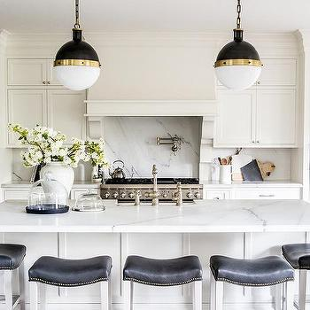 white kitchen island with black leather saddle counter stools