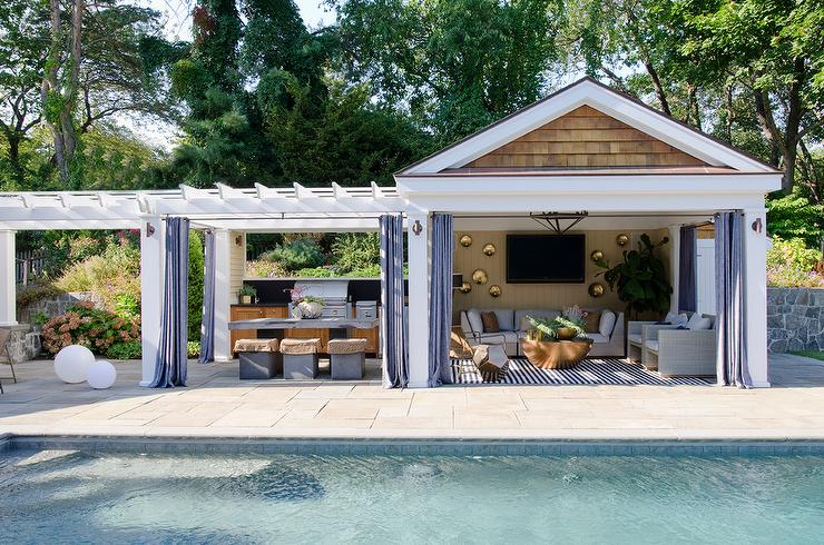 pool cabana next to outdoor kitchen pergola concrete dining table stools