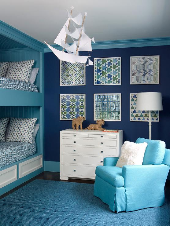 Two tone blue boys  shared bedroom features framed stacked blue and green  prints fixed on a navy blue wall  accented with turquoise blue molding. Navy Blue Boy Bedroom with Silver Race Car Bed   Transitional