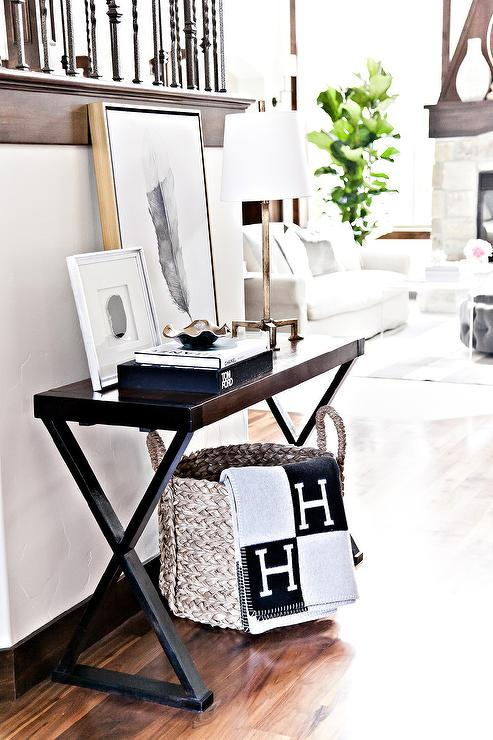 ... Basket Draped With A Black And Gray Hermes Avalon Blanket Tucked Under  A Dark Stained X Based Console Table Topped With Coffee Table Book And Art.