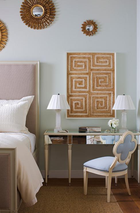 exquisitely decorated bedroom boasts a blue quatrefoil chair positioned on a bound sisal rug in front of mirrored desk topped with white alabaster lamps - Chair As Bedside Table