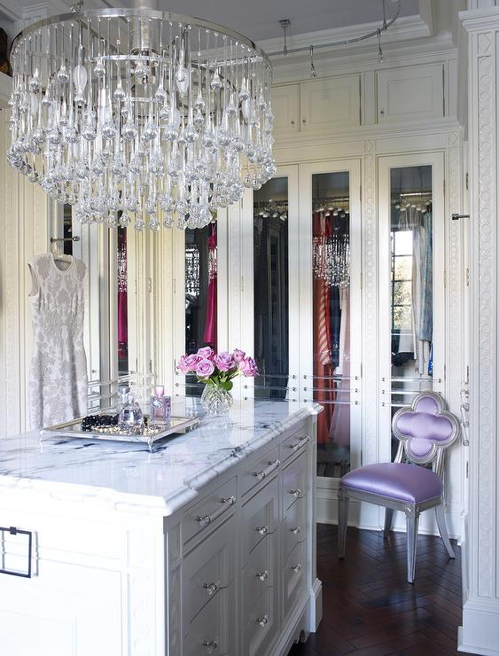 Glamorous White Walk In Closet Boasts A Large Tiered Crystal Chandelier Hung From Lilac Ceiling Over Marble Top Island Fitted With Glass And